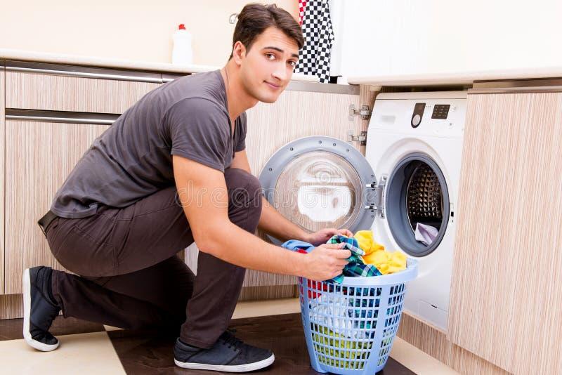 O homem novo do marido que faz a lavanderia em casa fotos de stock royalty free