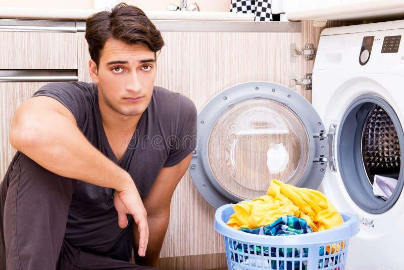 O homem novo do marido que faz a lavanderia em casa fotografia de stock