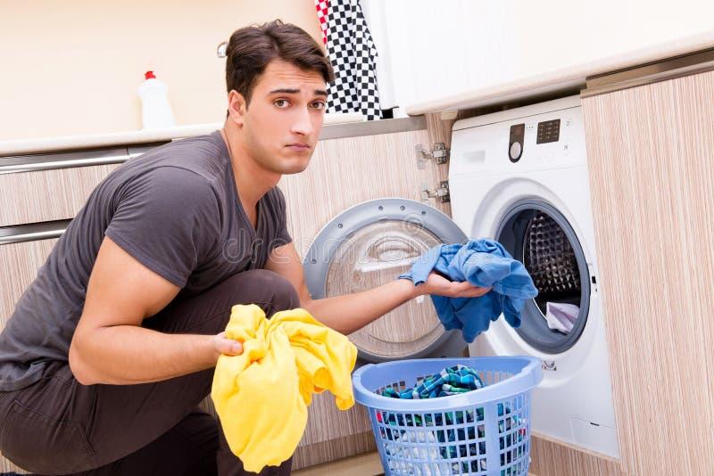 O homem novo do marido que faz a lavanderia em casa foto de stock royalty free