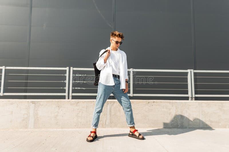 O homem novo do moderno urbano em uma camisa do vintage na calças de ganga em sandálias vermelhas em óculos de sol pretos com um  foto de stock