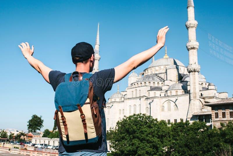 O homem novo do turista ao lado da mesquita azul mundialmente famosa em Istambul levantou suas mãos que mostram como feliz e livr imagem de stock