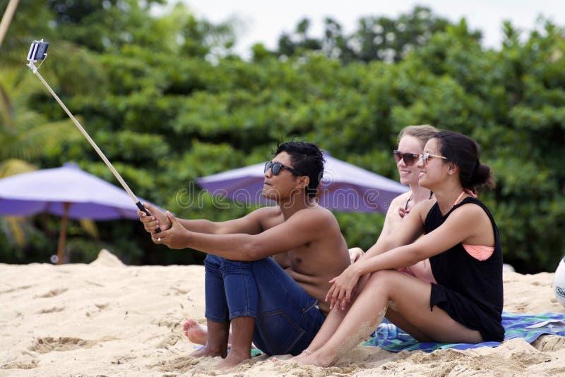 O homem novo e as mulheres que vestem óculos de sol tomam o selfi com utilização de uma vara do selfie na praia imagens de stock royalty free