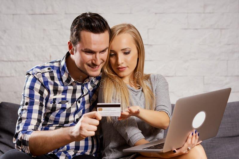 O homem novo e a mulher estão sentando-se no sofá e está comprando em linha foto de stock