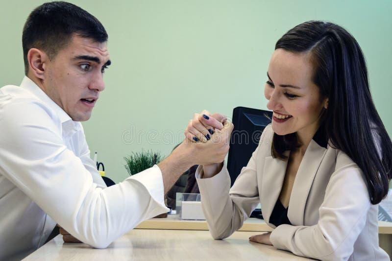 O homem novo e a mulher lutam em suas mãos na mesa no escritório por um chefe do lugar, cabeça A batalha dos sexos, hav novo dos  fotos de stock royalty free