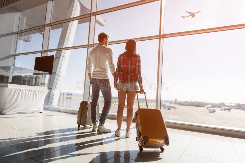 O homem novo e a mulher que olham o voo aplanam foto de stock