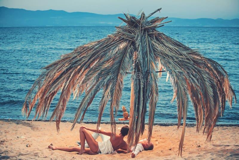 O homem novo e a mulher relaxam na areia morna por um mar e na vista a em algum lugar fotografia de stock royalty free