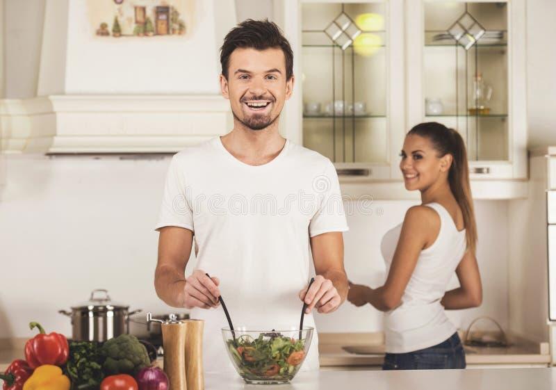 O homem novo e sua esposa estão preparando o jantar na cozinha imagem de stock