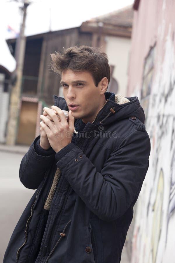 O homem novo elegante bebe o café na rua em um dia frio imagem de stock