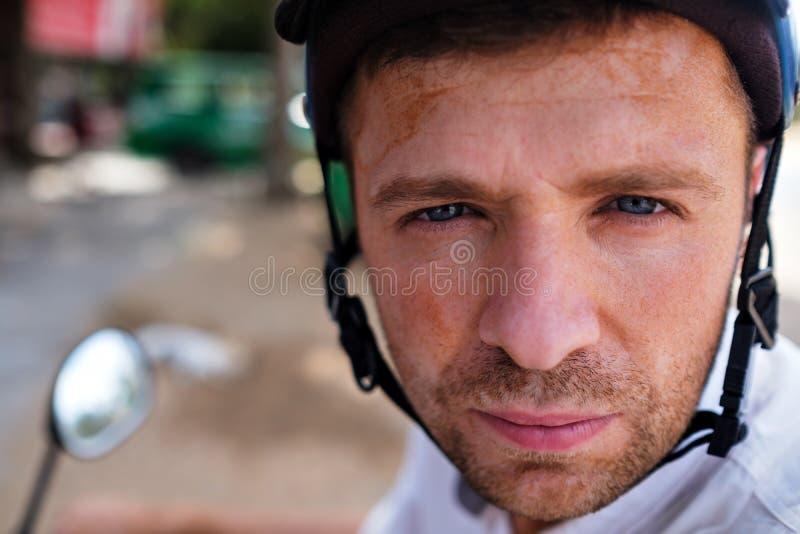 O homem novo em um capacete fica em uma estrada de Ásia que olha na câmera Está vestindo o capacete foto de stock royalty free