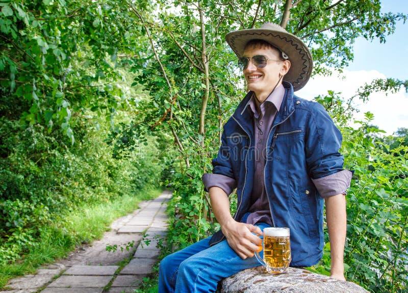 O homem novo em um chapéu e em óculos de sol de vaqueiro está bebendo a cerveja imagem de stock royalty free