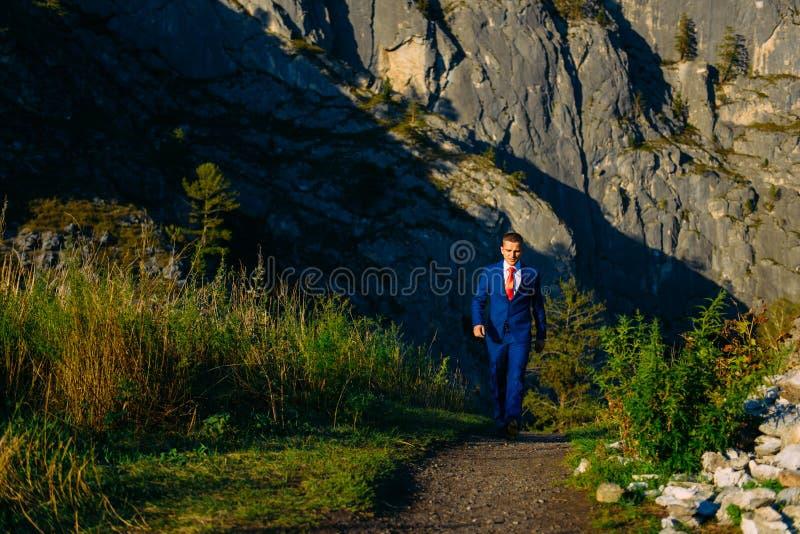 O homem novo em um terno de neg?cio com o la?o vermelho no fundo das montanhas vai a seu alvo em um dia de ver?o ensolarado imagem de stock royalty free