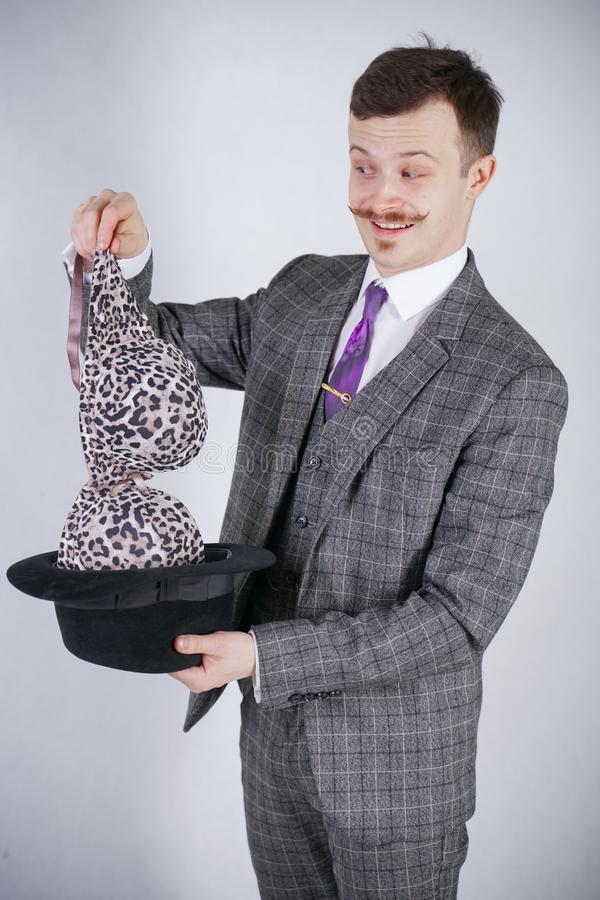 O homem novo em um terno de negócio retira o sutiã do leopardo de seu chapéu, mas quis truques com maravilha e riqueza o homem em fotografia de stock royalty free