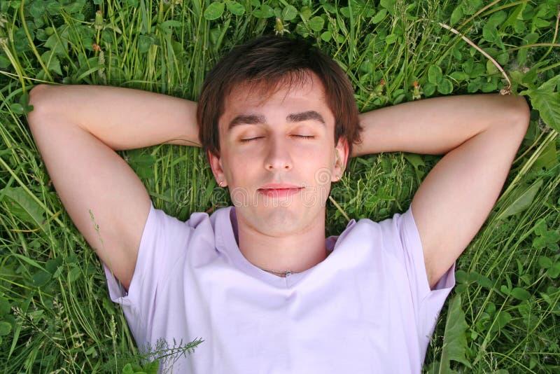 O homem novo encontra-se na cabeça da grama nos olhos fechados as mãos fotografia de stock