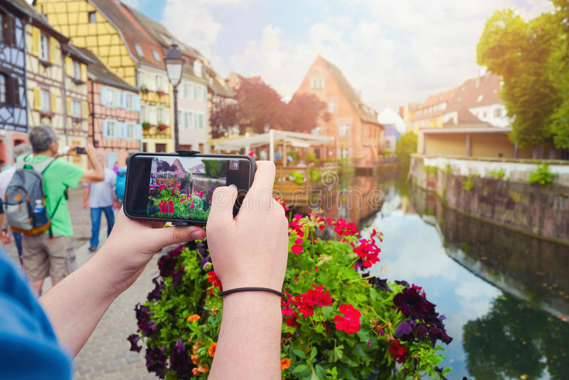 O homem novo entrega guardar o smartphone e tomar a imagem da foto da cidade bonita Colmar, França fotografia de stock