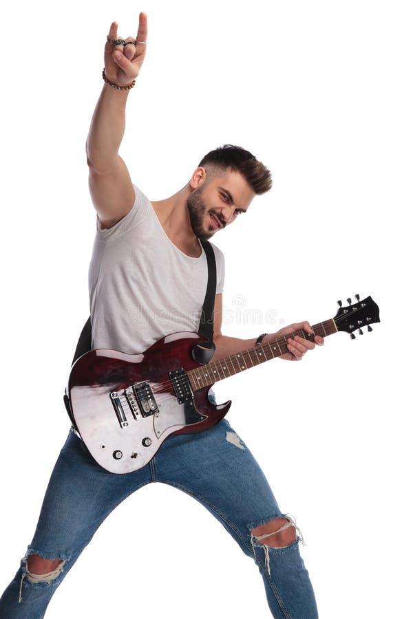 O homem novo entusiasmado com guitarra faz a rocha no sinal fotografia de stock royalty free