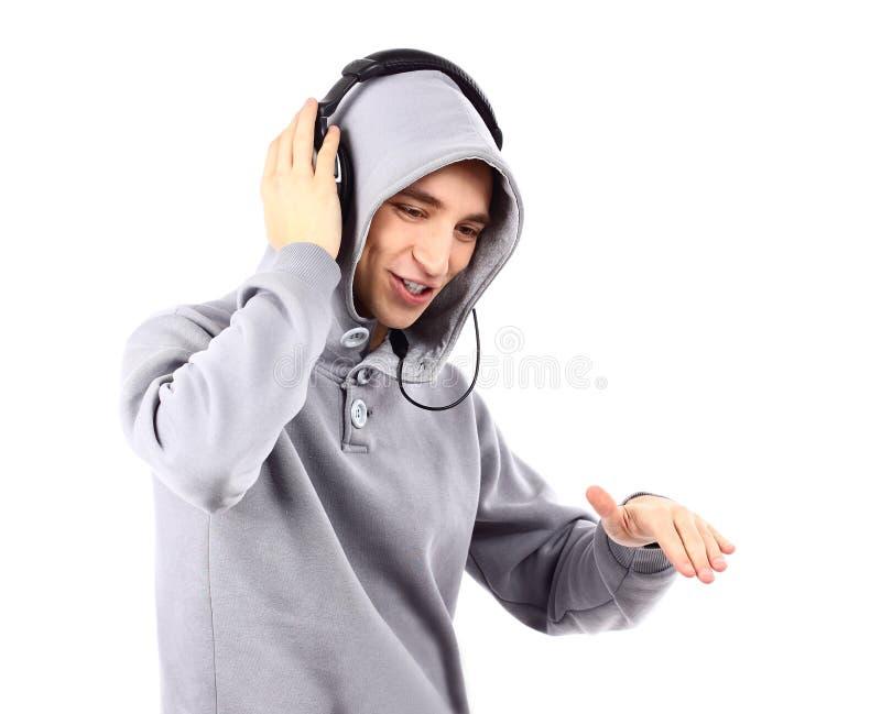 O homem novo escuta música com auscultadores imagens de stock royalty free
