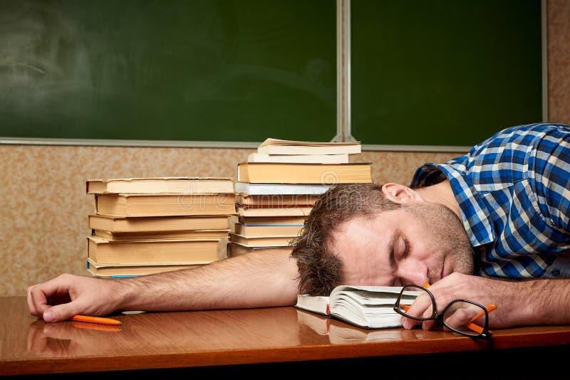 O homem novo esgotado dorme no livro aberto imagem de stock royalty free