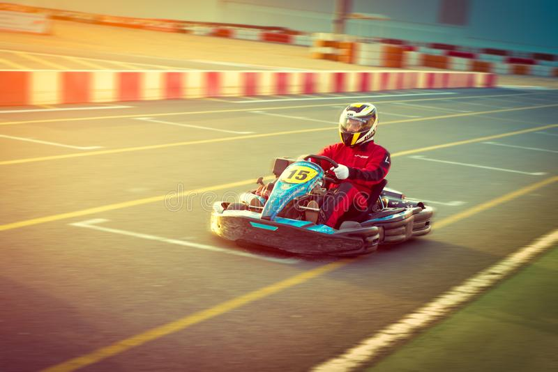 O homem novo está conduzindo vai-kart carro com velocidade em uma trilha de competência do campo de jogos imagem de stock