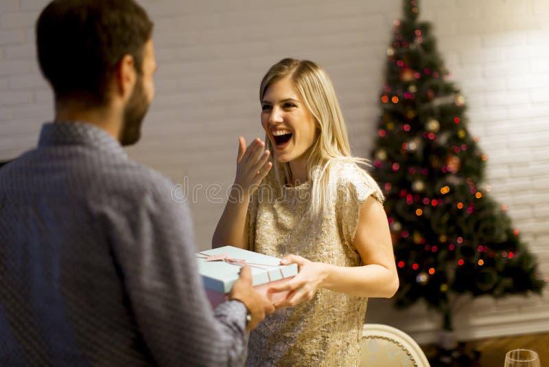 O homem novo está dando um presente a sua amiga bonita fotografia de stock