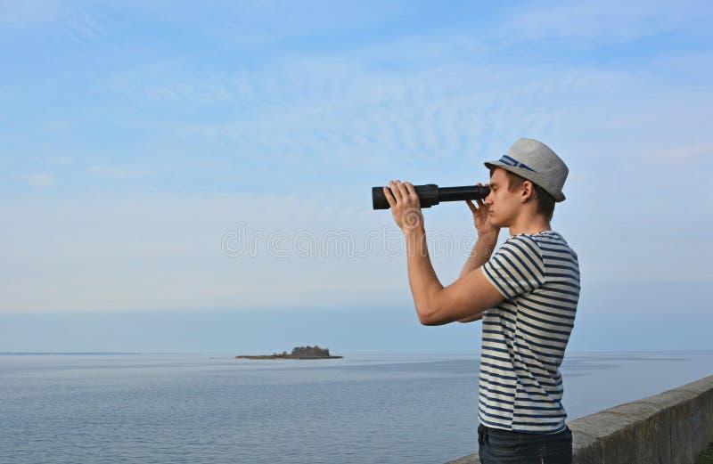 O homem novo está olhando através do telescópio pequeno no s fotos de stock royalty free