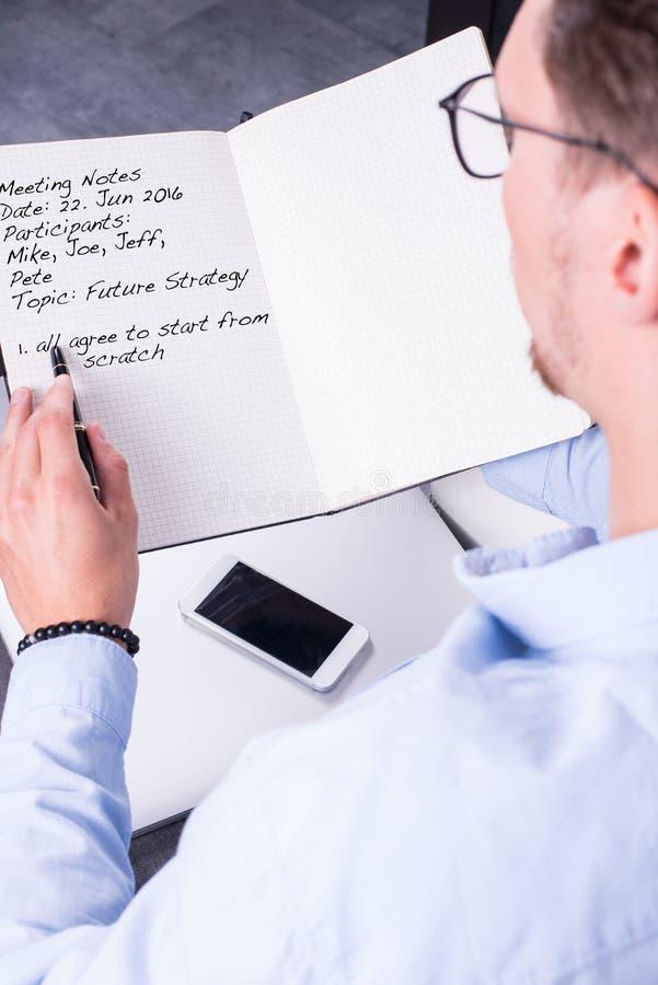 O homem novo está tomando notas da reunião no caderno aberto imagens de stock