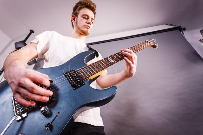 O homem novo est? jogando a guitarra el?trica imagens de stock royalty free