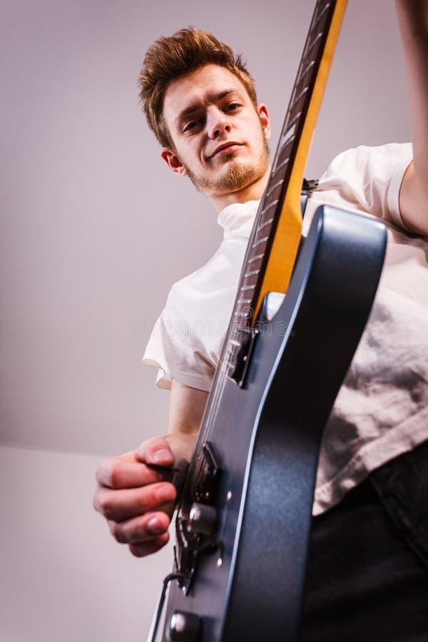 O homem novo est? jogando a guitarra el?trica imagens de stock