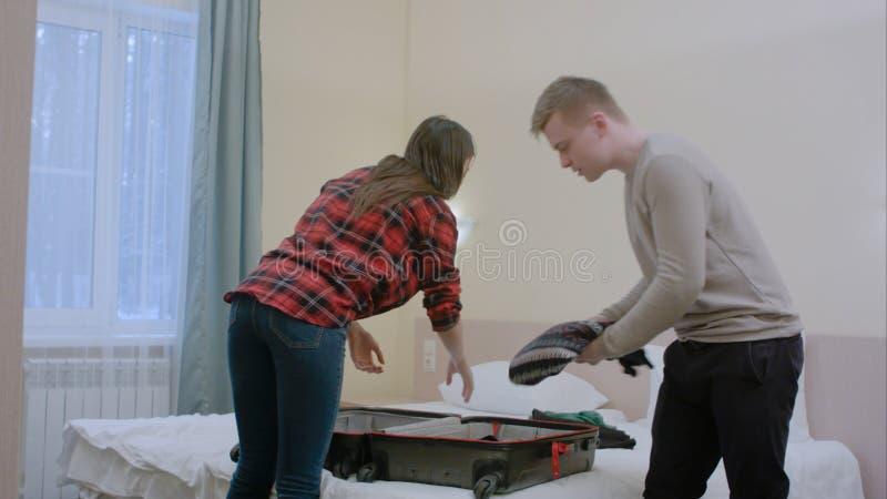 O homem novo estiver irritado, quando ele e sua amiga que embalam uma mala de viagem para uma viagem imagem de stock