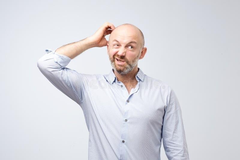 O homem novo farpado europeu maduro vestiu-se na camisa branca ocasional que tenta recordar aonde pôs as chaves do carro foto de stock