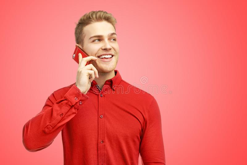 O homem novo farpado positivo sorri o sorriso neve-branco, vestido na camisa vermelha Indivíduo considerável contente de falar co fotos de stock royalty free