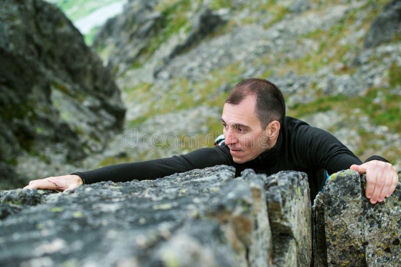 O homem novo faz duramente a escalada de uma rocha íngreme sem corda foto de stock royalty free