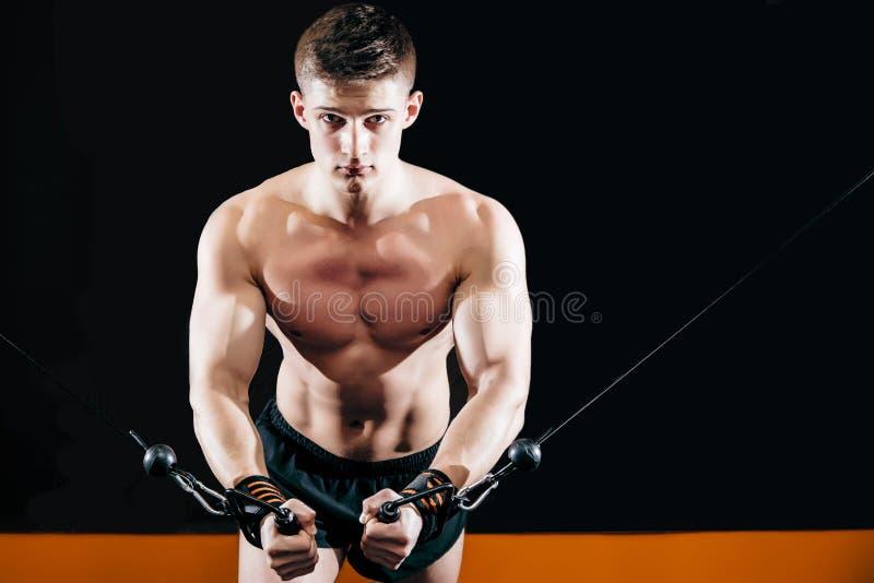 O homem novo faz o mão-corte no simulador no gym Exercite para os músculos do cruzamento da caixa foto de stock royalty free