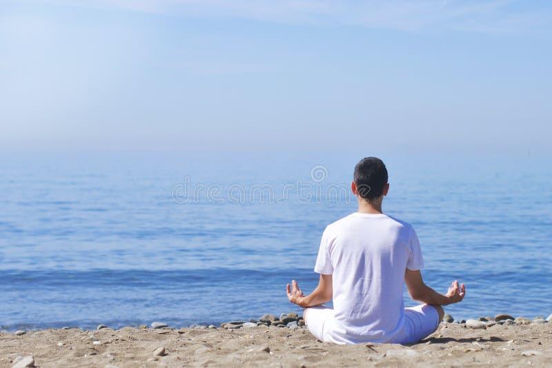 O homem novo faz a meditação na pose dos lótus no mar/na praia, na harmonia e projeto do oceano Ioga praticando do menino no recu imagem de stock