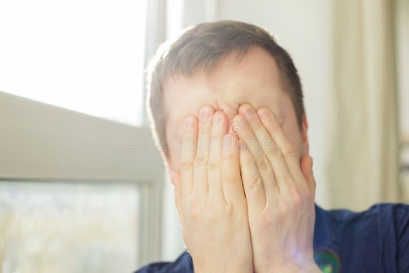 O homem novo fecha sua cara no esforço e na depressão fotos de stock