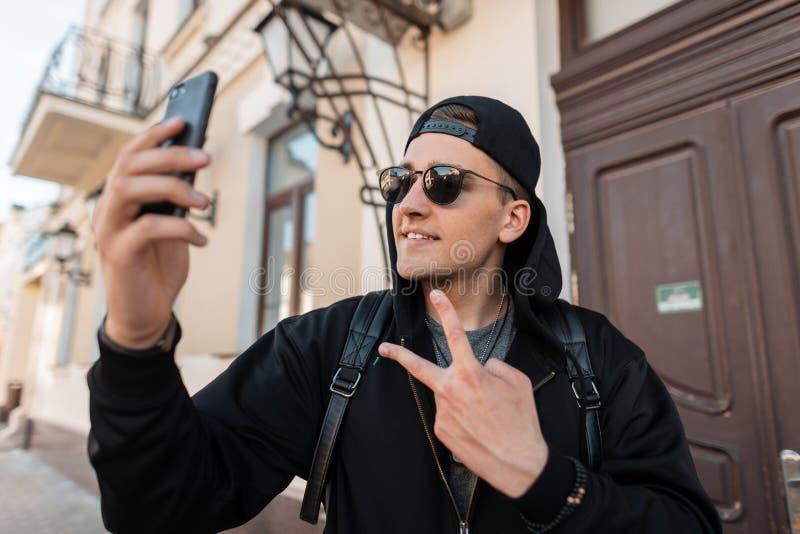 O homem novo feliz atrativo do moderno com um sorriso bonito na roupa preta elegante em um tampão nos óculos de sol faz um selfie imagens de stock royalty free