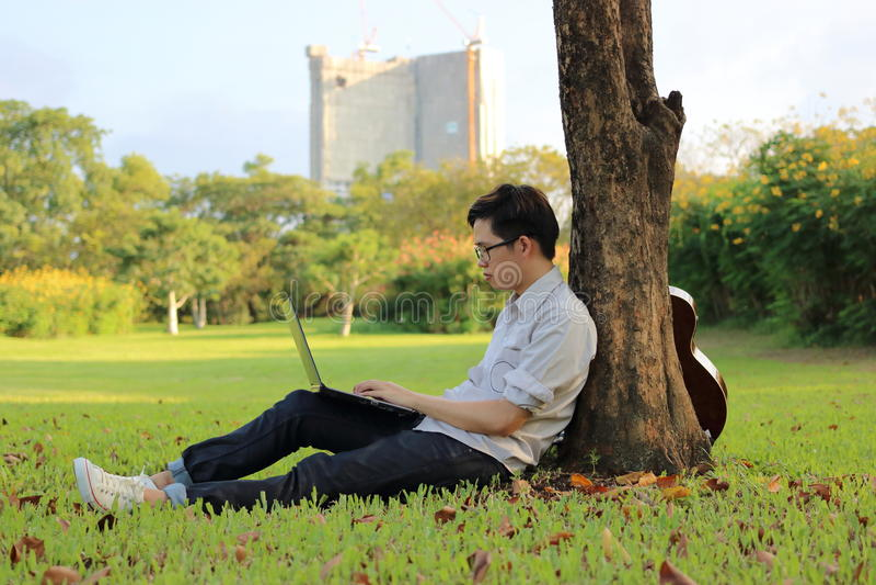 O homem novo feliz está usando um laptop no parque da cidade fotografia de stock royalty free