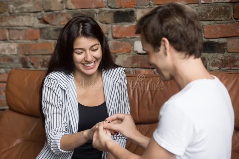 O homem novo feliz propõe a sua amiga que senta-se no sofá imagens de stock