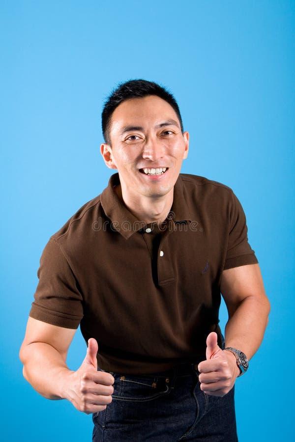 O homem novo feliz que mostra os polegares levanta o sinal fotografia de stock