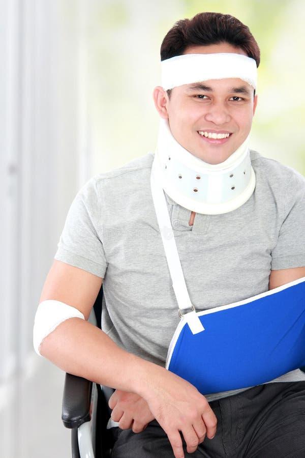 O homem novo ferido na cadeira de rodas ainda olha feliz fotografia de stock
