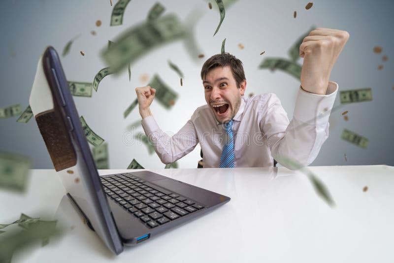 O homem novo ganha uma loteria em linha O dinheiro está caindo de cima de Conceito de aposta em linha imagens de stock royalty free