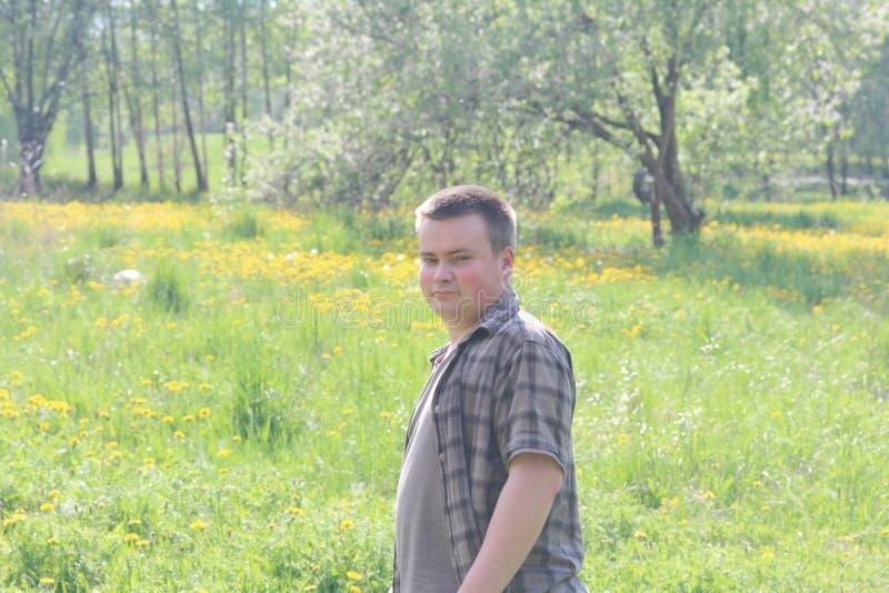 O homem novo girou para trás, andando ao longo de um prado da mola com a grama nova luxúria Disparado no luminoso fotografia de stock