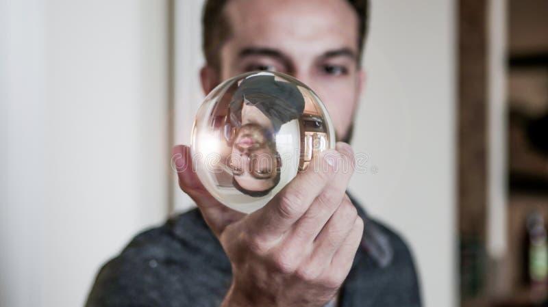 O homem novo guarda a bola de cristal na frente da cara fotos de stock