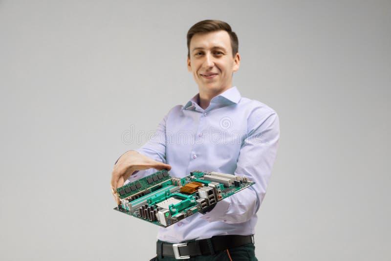 O homem novo guarda RAM e o cartão-matriz em suas mãos isoladas em um fundo claro imagens de stock royalty free