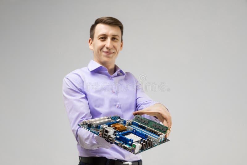 O homem novo guarda RAM e o cartão-matriz em suas mãos isoladas em um fundo claro foto de stock royalty free