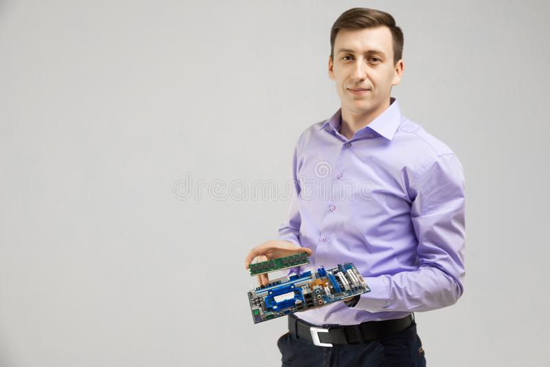 O homem novo guarda RAM e o cartão-matriz em suas mãos isoladas em um fundo claro imagem de stock