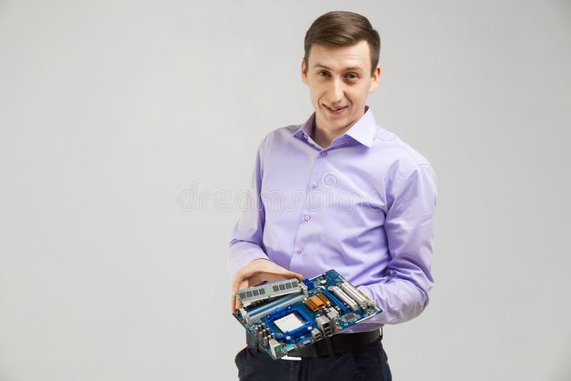 O homem novo guarda RAM e o cartão-matriz em suas mãos isoladas em um fundo claro fotografia de stock