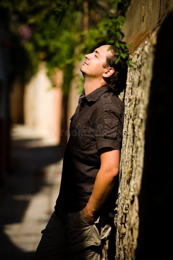 O homem novo inclina a parede de pedra na rua imagem de stock