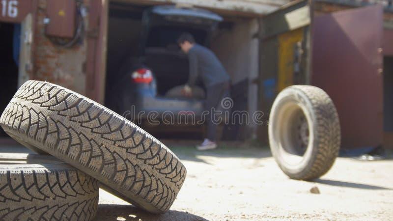 O homem novo joga afastado a roda de seu tronco de carro fotos de stock
