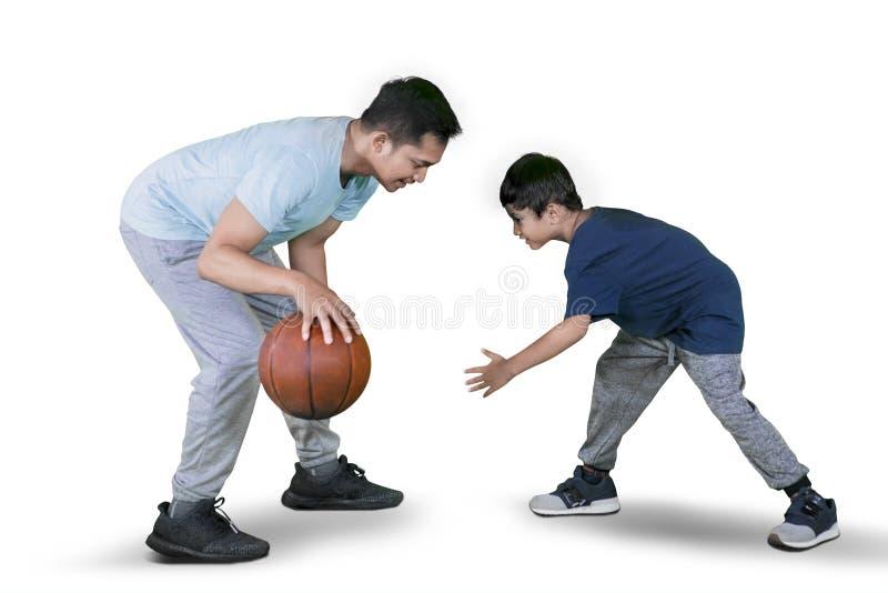 O homem novo joga o basquetebol com seu filho no estúdio imagem de stock