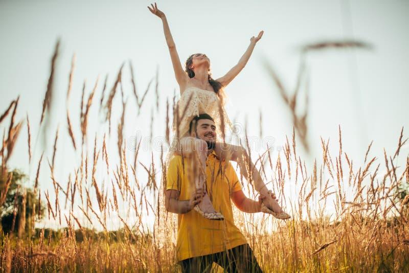 O homem novo leva a menina em seus ombros no prado imagens de stock royalty free